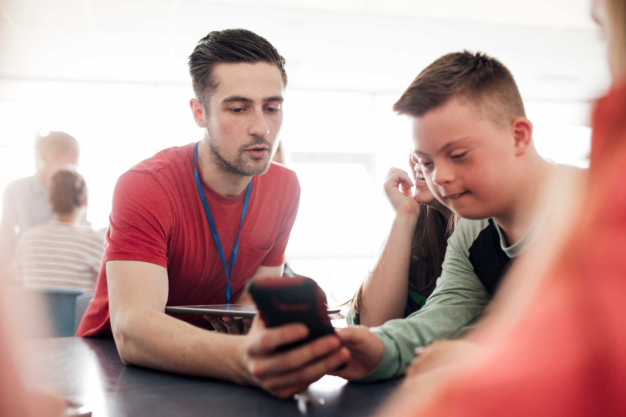 Teenage boy with Down Syndrome looking at mobile phone with young male adult